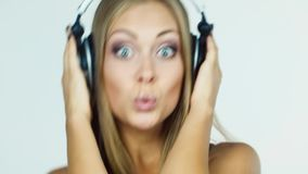 Ξανθό κορίτσι που ακούει τη μουσική στα ακουστικά και που χορεύει εντατικά απόθεμα βίντεο