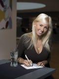 Ξανθό κορίτσι που γράφει στο ημερολόγιο στον καφέ Στοκ Εικόνα