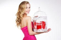 Ξανθό κορίτσι που κρατά το άσπρο κλουβί με την κόκκινη καρδιά Στοκ εικόνα με δικαίωμα ελεύθερης χρήσης
