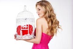 Ξανθό κορίτσι που κρατά το άσπρο κλουβί με την κόκκινη καρδιά Στοκ φωτογραφία με δικαίωμα ελεύθερης χρήσης