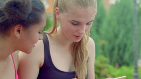 Ξανθό κορίτσι που μιλά με τη φίλη afro στο πάρκο φιλμ μικρού μήκους