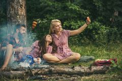 Ξανθό κορίτσι που παίρνει selfie στους δασικούς χαμογελώντας φίλους που θέτουν με τα λουκάνικα Νεαροί που στρατοπεδεύουν στα ξύλα στοκ εικόνες με δικαίωμα ελεύθερης χρήσης