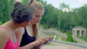 Ξανθό κορίτσι που παρουσιάζει φωτογραφίες στην ταμπλέτα στην αφρικανική φίλη απόθεμα βίντεο