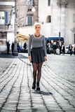 Ξανθό κορίτσι που περπατά στην οδό στην πόλη που φορά μια φούστα Στοκ εικόνα με δικαίωμα ελεύθερης χρήσης