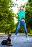 Ξανθό κορίτσι που πηδά κοντά στο αγαπημένο σκυλί της ή Στοκ Φωτογραφία