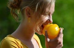 Ξανθό κορίτσι που τρώει το κίτρινο πιπέρι Στοκ εικόνα με δικαίωμα ελεύθερης χρήσης