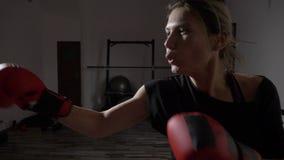 Ξανθό κορίτσι που χτυπά τη punching τσάντα νευρικά στη γυμναστική μετά από να χωρίσει με το φίλο της σε σε αργή κίνηση - απόθεμα βίντεο