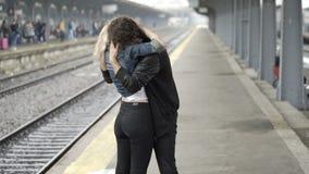 Ξανθό κορίτσι που ψάχνει το φίλο που φιλά τον και που παρουσιάζει έπειτα αγάπη της στο σταθμό τρένου απόθεμα βίντεο