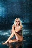 Ξανθό κορίτσι σε ένα κοστούμι λουσίματος στο νερό στοκ φωτογραφία