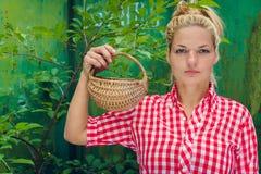 Ξανθό κορίτσι σε ένα πράσινο καλάθι εκμετάλλευσης υποβάθρου Στοκ εικόνες με δικαίωμα ελεύθερης χρήσης