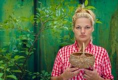 Ξανθό κορίτσι σε ένα πράσινο καλάθι εκμετάλλευσης υποβάθρου Στοκ Φωτογραφίες