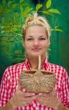 Ξανθό κορίτσι σε ένα πράσινο καλάθι εκμετάλλευσης υποβάθρου Στοκ Φωτογραφία