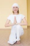 Ξανθό κορίτσι στην άσπρη γιόγκα άσκησης στη θέση Ardha Padmasana Στοκ εικόνα με δικαίωμα ελεύθερης χρήσης
