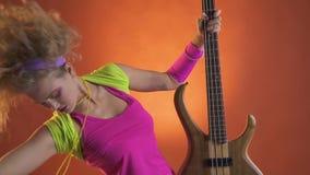 Ξανθό κορίτσι στην εξάρτηση της δεκαετίας του '80 που χορεύει και που απολαμβάνει τη μουσική με μια κιθάρα φιλμ μικρού μήκους