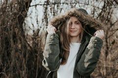 Ξανθό κορίτσι στο θερμό και πράσινο χειμερινό σακάκι με την κουκούλα γουνών στοκ φωτογραφίες