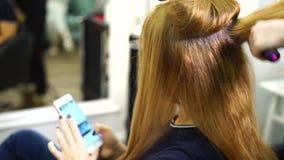 Ξανθό κορίτσι στο στιλίστα τρίχας, με ένα smartphone απόθεμα βίντεο