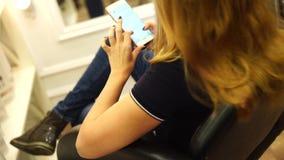 Ξανθό κορίτσι στο στιλίστα τρίχας, με ένα smartphone φιλμ μικρού μήκους