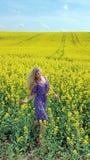 Ξανθό κορίτσι στο φόρεμα με την τυπωμένη ύλη λουλουδιών στον ανθίζοντας κίτρινο τομέα συναπόσπορων Στοκ εικόνες με δικαίωμα ελεύθερης χρήσης