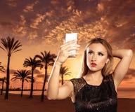 Ξανθό κορίτσι τουριστών που παίρνει τις φωτογραφίες του ηλιοβασιλέματος της Μαγιόρκα Στοκ Εικόνες