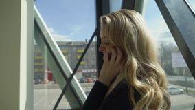 Ξανθό κορίτσι Beautisul στη μαύρη υπεράσπιση το παράθυρο και την ομιλία στο τηλέφωνο φιλμ μικρού μήκους