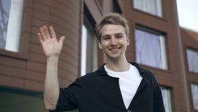 Ξανθό κυματίζοντας χέρι νεαρών άνδρων που στέκεται κοντά στο σπίτι του απόθεμα βίντεο