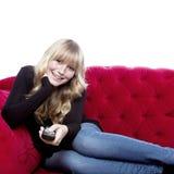 Ξανθό μαλλιαρό κορίτσι στον καναπέ ευχαριστημένο από απομακρυσμένο Στοκ φωτογραφίες με δικαίωμα ελεύθερης χρήσης