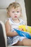 Ξανθό μαλλιαρό μπλε Eyed μικρό κορίτσι που διαβάζει το βιβλίο της στοκ εικόνα