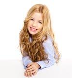 Ξανθό μικρό κορίτσι κατσικιών που χαμογελά σε ένα γραφείο στο λευκό Στοκ εικόνα με δικαίωμα ελεύθερης χρήσης