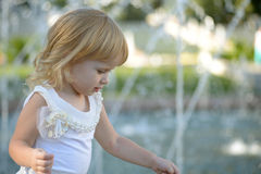Ξανθό μικρό κορίτσι σε ένα πάρκο κοντά στην πηγή στοκ φωτογραφίες με δικαίωμα ελεύθερης χρήσης