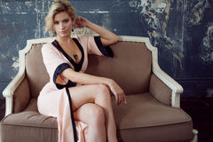 ξανθό μοντέλο τριχώματος μό&del Νέα ελκυστική γυναίκα, που εγκαθιστά στον καναπέ, εκλεκτής ποιότητας ύφος Στοκ Εικόνα