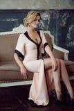 ξανθό μοντέλο τριχώματος μό&del Νέα ελκυστική γυναίκα, που εγκαθιστά στον καναπέ, εκλεκτής ποιότητας ύφος στοκ φωτογραφία