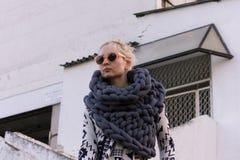 Ξανθό νέο όμορφο κορίτσι μόδας που φορά το των Αζτέκων γραπτό σακάκι και το πλεκτό γκρίζο μαντίλι φανέλλων Εξάρτηση φεστιβάλ Στοκ Φωτογραφία
