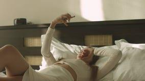 Ξανθό να βρεθεί στο κρεβάτι και λήψη selfie στο δωμάτιο ξενοδοχείου απόθεμα βίντεο