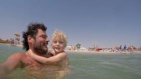 Ξανθό παιχνίδι μικρών κοριτσιών στο νερό με το βίντεο πατέρων της απόθεμα βίντεο