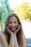 Ξανθό πρότυπο χαμόγελου με τη σκόνη Gulal χρώματος στο πρόσωπό της Στοκ εικόνα με δικαίωμα ελεύθερης χρήσης