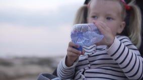 Ξανθό πόσιμο νερό μικρών κοριτσιών από ένα πλαστικό μπουκάλι στο θερινό πάρκο απόθεμα βίντεο