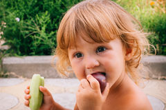 Ξανθό σγουρό κορίτσι που έχει τη διασκέδαση που τρώει ένα δαμάσκηνο Στοκ εικόνες με δικαίωμα ελεύθερης χρήσης