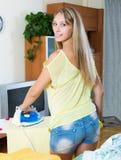 Ξανθό σιδέρωμα γυναικών με το σίδηρο Στοκ εικόνες με δικαίωμα ελεύθερης χρήσης