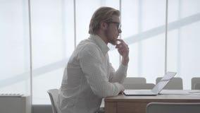 Ξανθό στοχαστικό άτομο στα γυαλιά που κάθονται στον πίνακα σε ένα ελαφρύ άνετο γραφείο μπροστά από το netbook και που κτυπούν δικ φιλμ μικρού μήκους