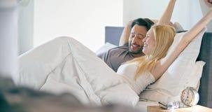 Ξανθό τέντωμα γυναικών και ανδρών μετά από τον ύπνο Ερωτευμένο πρωί ζεύγους ξυπνήστε στο σπίτι στην κρεβατοκάμαρα Καυκάσια φίλη κ απόθεμα βίντεο