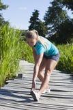 Ξανθό τέντωμα κοριτσιών ικανότητας κάτω από τα πόδια και την πλάτη της, υπαίθρια Στοκ φωτογραφίες με δικαίωμα ελεύθερης χρήσης