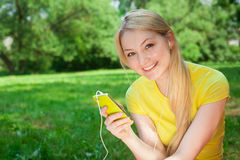 Ξανθό τηλέφωνο κυττάρων εκμετάλλευσης κοριτσιών και μουσική ακούσματος με το headphon Στοκ Φωτογραφία