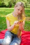 Ξανθό τηλέφωνο κυττάρων εκμετάλλευσης κοριτσιών και μουσική ακούσματος με το headphon Στοκ εικόνα με δικαίωμα ελεύθερης χρήσης