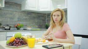 Ξανθό τσάι κατανάλωσης με croissant στο σπίτι στην κουζίνα του απόθεμα βίντεο