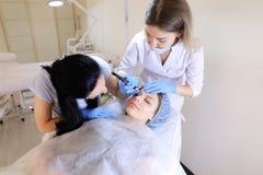 Ξανθό cosmetologist που κάνει το μόνιμο makeup για τη γυναίκα στο γραφείο με τη νοσοκόμα στοκ φωτογραφία με δικαίωμα ελεύθερης χρήσης