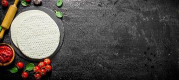 Ξεδιπλωμένη ζύμη πιτσών με τον τοματοπολτό, το σπανάκι και το κεράσι στοκ εικόνες