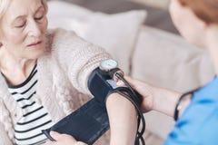 Ξελεπιασμένη επάνω άποψη σχετικά με τη νοσοκόμα που μετρά την πίεση της ανώτερης γυναίκας Στοκ εικόνα με δικαίωμα ελεύθερης χρήσης