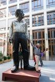 Ξεναγός από το άγαλμα του μεγάλου και μικρού ατόμου στην είσοδο φραγμών Στοκ Εικόνα