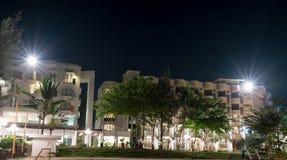 Ξενοδοχείο σε ένα παραθαλάσσιο θέρετρο κατά τη διάρκεια της νύχτας με τα φωτεινά φω'τα και των δέντρων με το σαφείς ουρανό και τα στοκ εικόνες