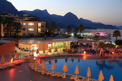 Ξενοδοχείο, βουνά και θάλασσα επάνω από το φωτεινό ήρεμο να επιθυμήσει σύννεφων πόλεων σκοτεινό βραδιού ηλιοβασίλεμα φωτός του ήλ Στοκ φωτογραφίες με δικαίωμα ελεύθερης χρήσης